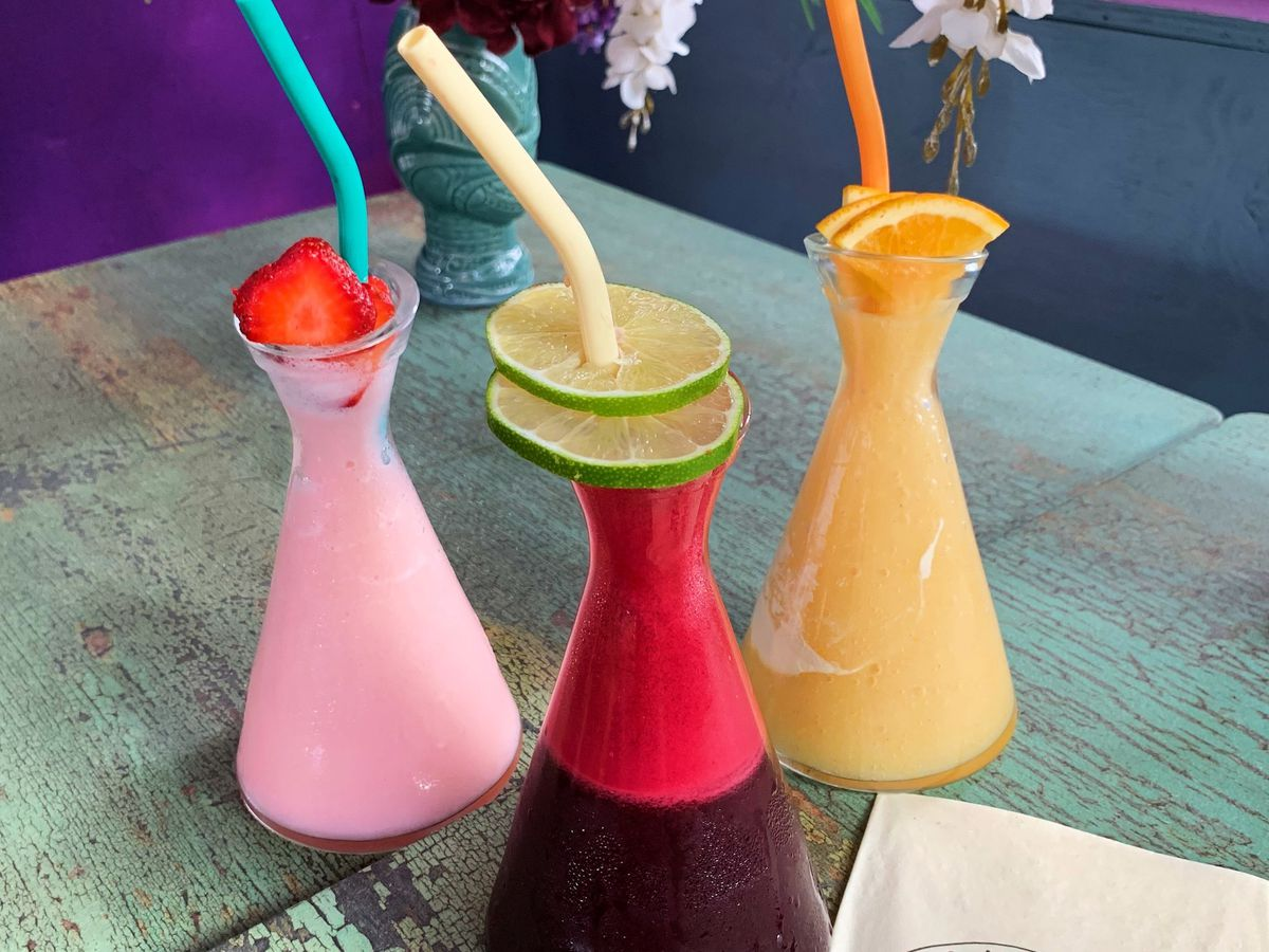 Three brightly colored frozen cocktails