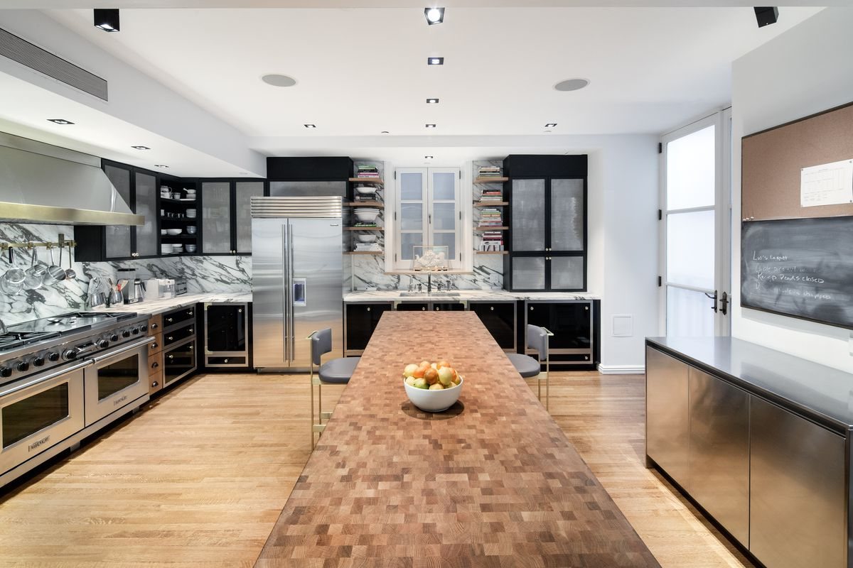A kitchen with a long butcher block-topped island, black cabinets, streaky marble countertops and backsplashes and stainless steel appliances.