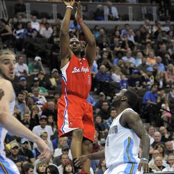 Los Angeles Clippers guard Chris Paul, center, shoots against Denver Nuggets guard Ty Lawson, right, during the third quarter of an NBA basketball game on Wednesday, April 18, 2012, in Denver.