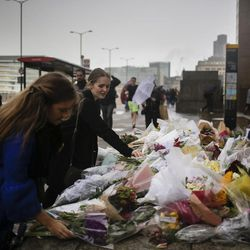 Women place bouquets of flowers on a memorial for victims at the London Bridge in London, Tuesday, June 6, 2017. British police on Tuesday named the third London Bridge attacker as an Italian national of Moroccan descent, and Italian officials said they had passed on their concerns about him to British intelligence officials last year.