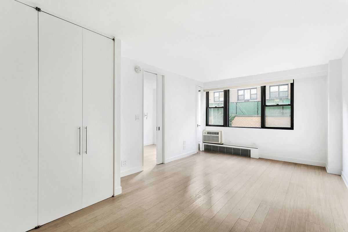 A living area with hardwood floors, a closet on the left, and a large window in the back.