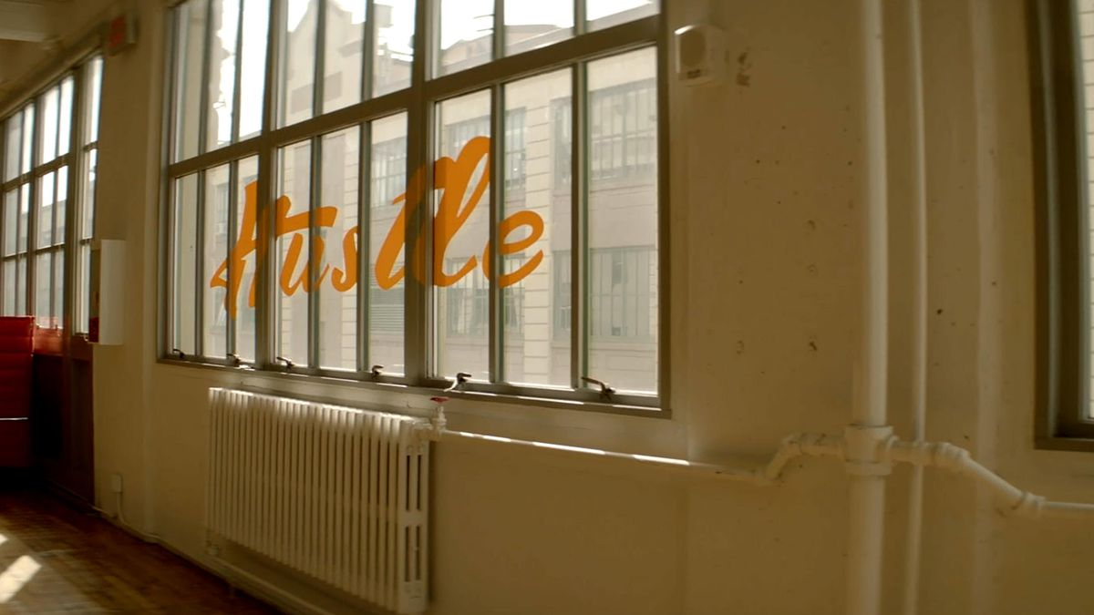 "A window printed with cursive lettering reading ""Hustle."""