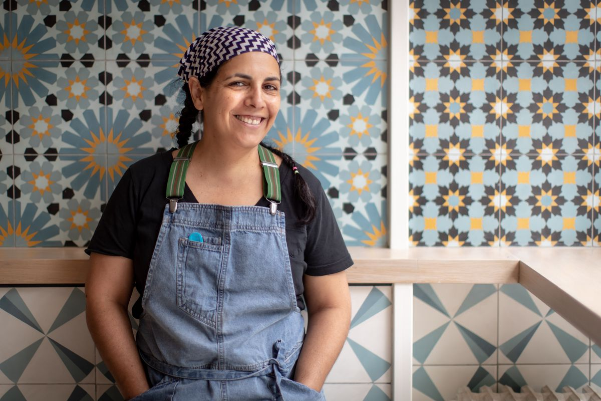Einat Admony in front of Kish-Kash's colorful pale blue patterned walls