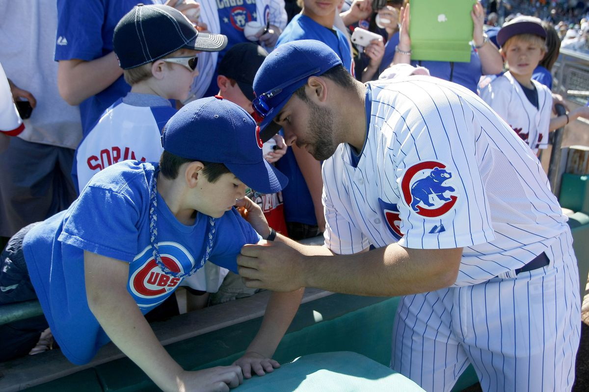 """David DeJesus complies with a young fan's request to sign """"just under the tattoo of the biker girl holding the beer bottle""""."""