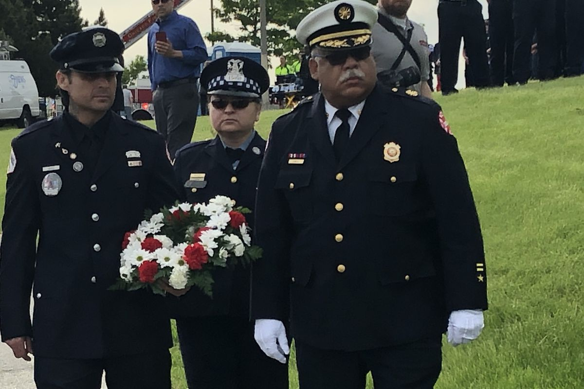 Chicago Fire Commissioner Richard C. Ford II escorts the siblings of fallen firefighter Juan Bucio, Isaac, a fellow Chicago firefighter, and Maria, a Chicago police officer, during a wreath-laying ceremony Tuesday on the first anniversary of Juan Bucio's