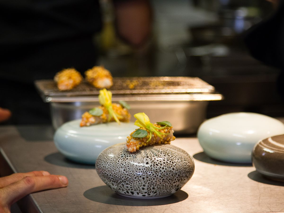 Two small dishes are plated on round stone-like pedestals sitting on a steel prep station with a cook's hands resting on the surface nearby