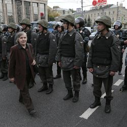 A woman walks past a line of police officers blocking a street during a protest march in Moscow, Saturday, Sept. 15, 2012. Thousands of protesters marched across downtown Moscow on Saturday in the first major rally in three months against President Vladimir Putin, while defying the Kremlin's ongoing efforts to crackdown on opposition. About 7,000 police officers were deployed to maintain security Saturday along the route of the march, which has been authorized by the city government.