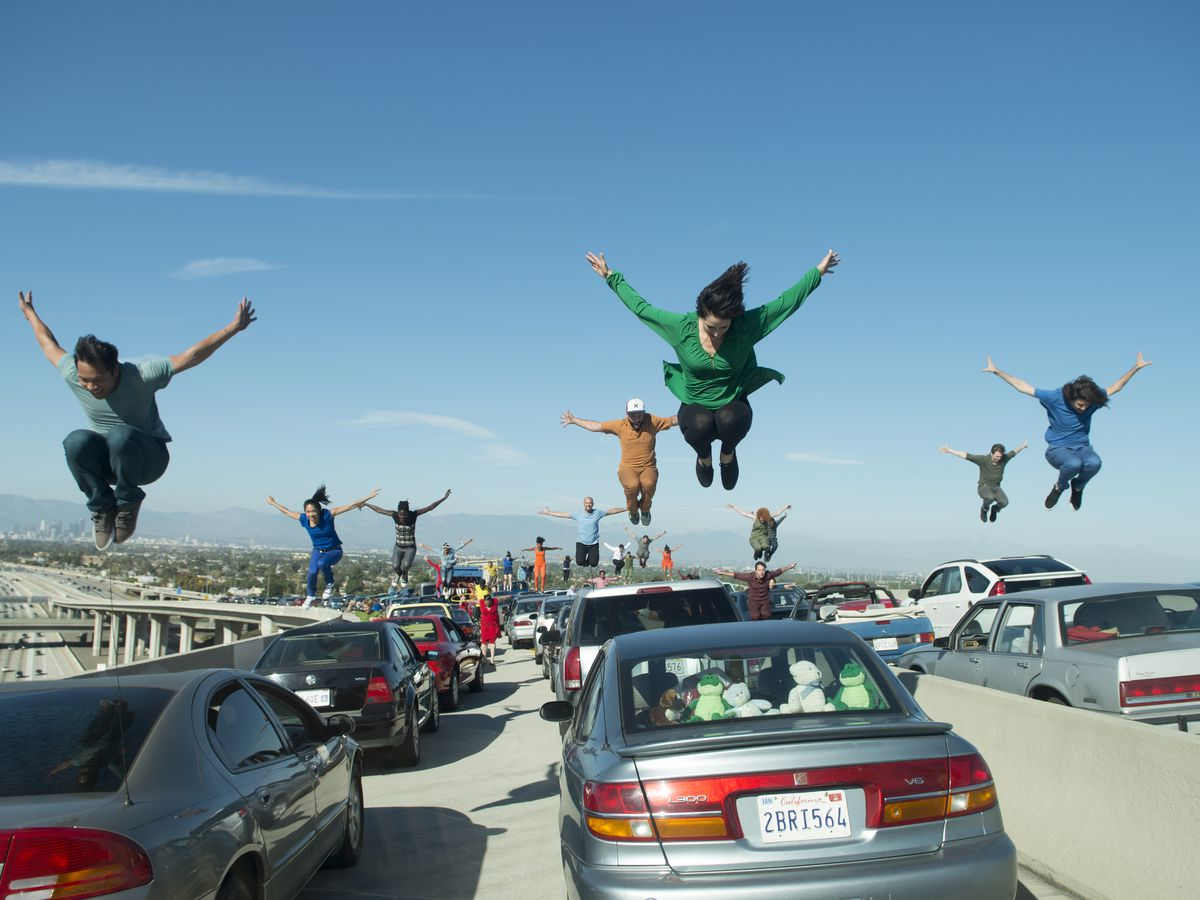 People joyfully jumping over cars standing still on a highway in Los Angeles. This is a dance number in the movie La La Land.