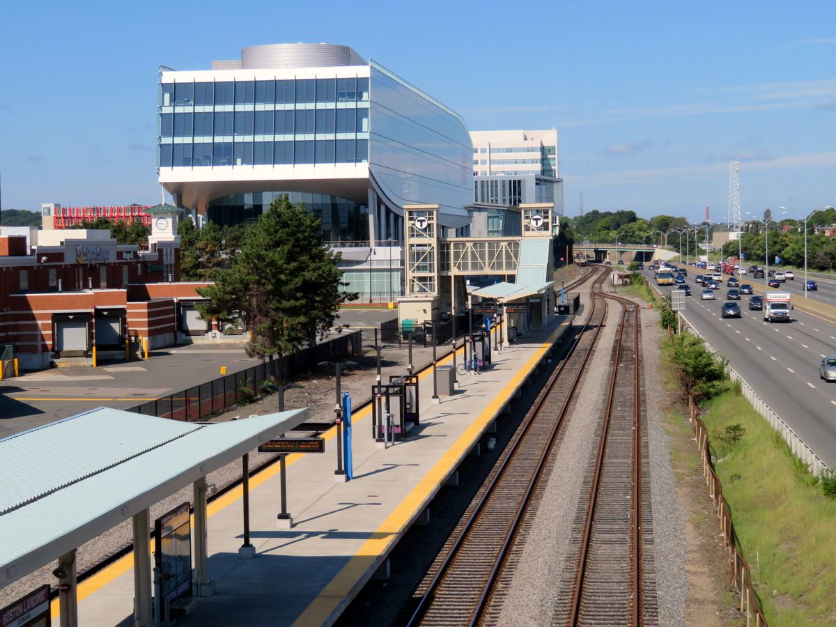 Wide view of a train platform next to a boxy, rectangular glass building along a highway.