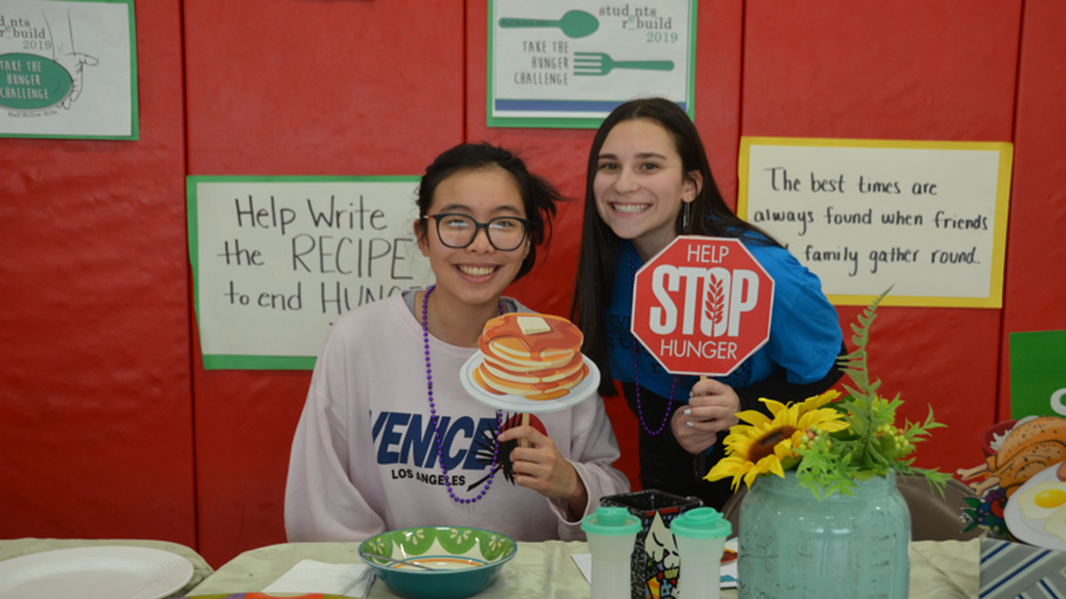 Two students pose at a school event to raise awareness about hunger