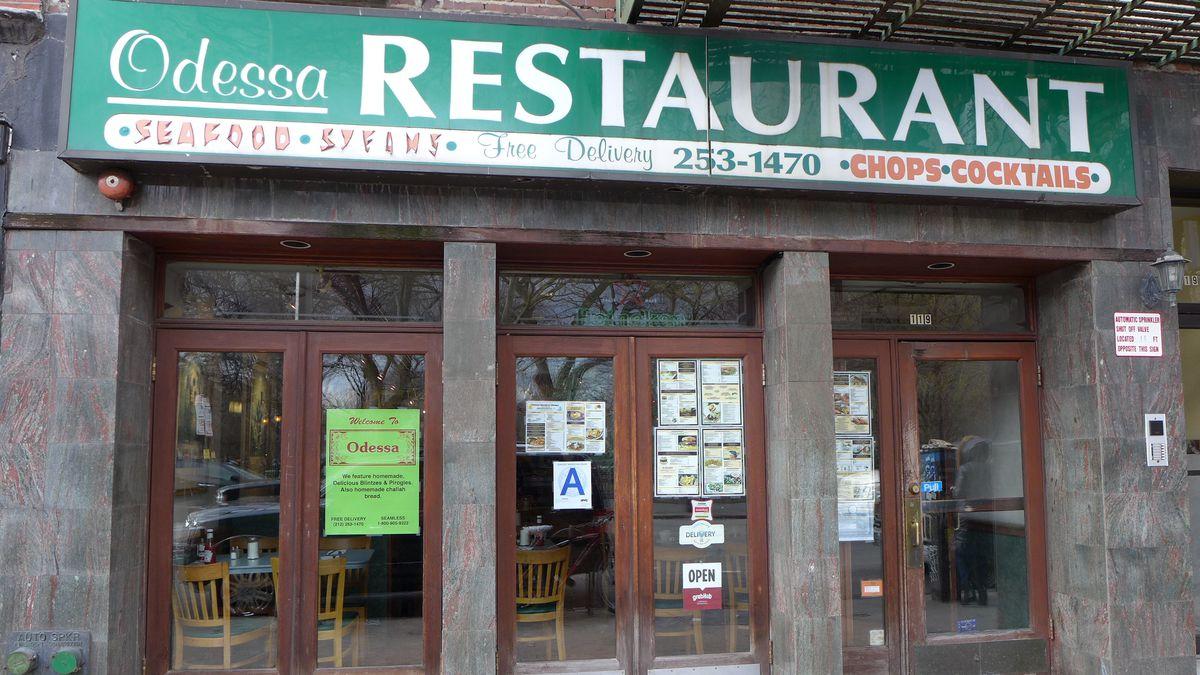 A marble facade with a green sign above.