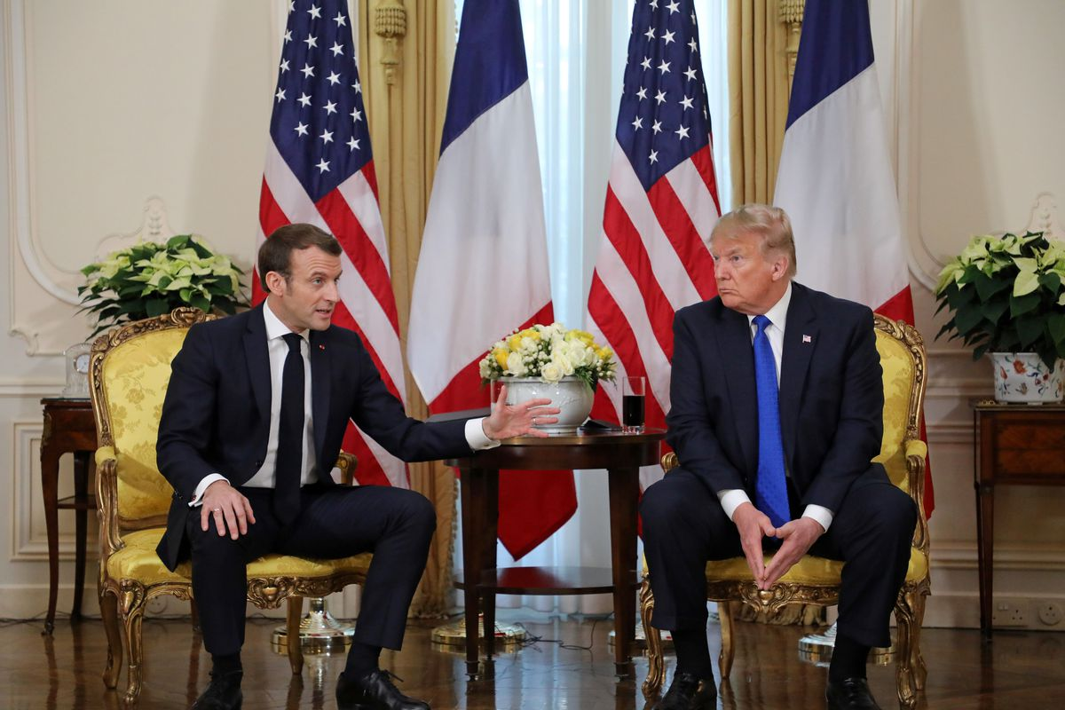 American President Donald Trump and French President Emmanuel Macron sit in armchairs on either side of a small table, with French and American flags behind them.