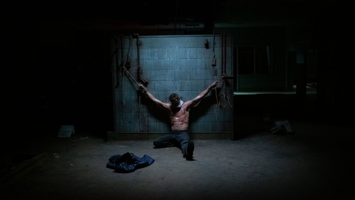 Chris Martin chained to a wall in Demonic