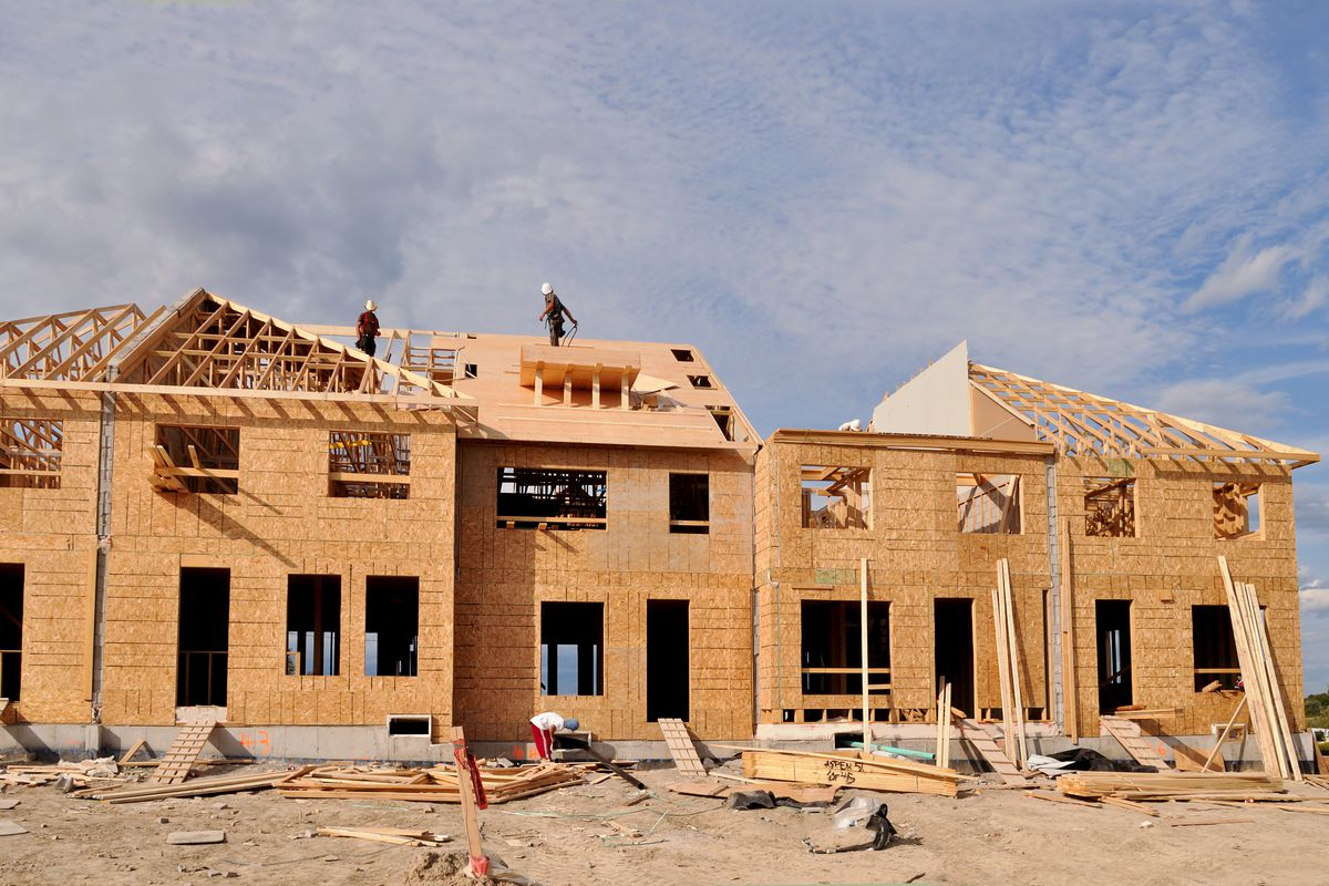 Construction workers at a job site consisting of a row of under-construction town homes with exposed wooden walls and incomplete roofs.