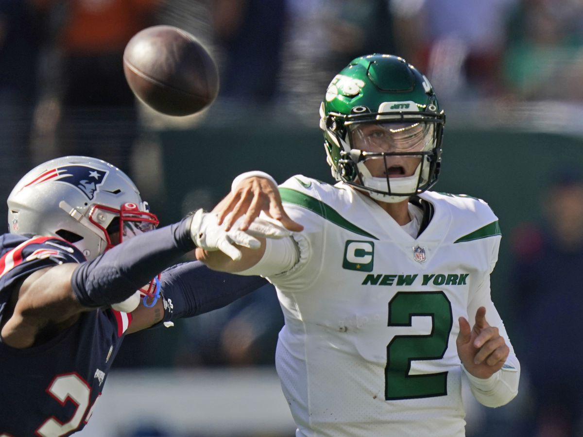 New York Jets quarterback Zach Wilson, right, throws under pressure from New England Patriots' Joejuan Williams during an NFL game.