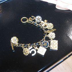Black leather and gold charm bracelet, $2,000