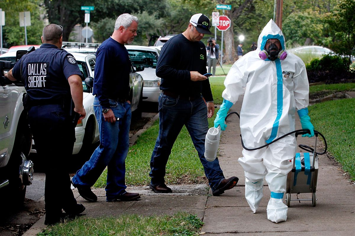 A man dressed in protective hazmat clothing leaves after treating the front porch and sidewalk of an apartment where a Texas nurse diagnosed with the Ebola virus lives.