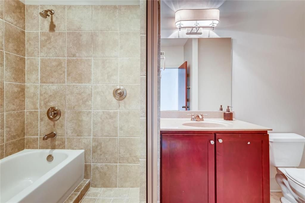 A bathroom with tub/shower combo, double vanity, and toilet.