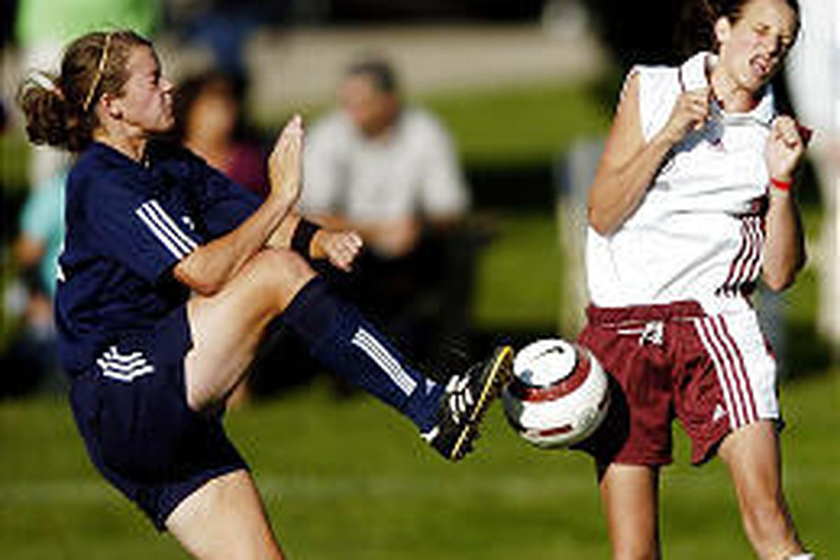 Timpanogos' Stacy Bartholomew, left, kicks ball as Mountain View's Anjie Lines tries to get out of the way.