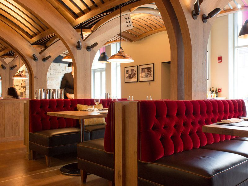 A restaurant interior featuring red booths and a light wooden ceiling embellished with arches