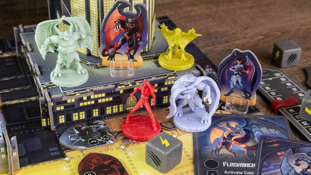 A collection of Gargoyles miniatures with assorted custom stone-colored dice, cards, and a 3D building that rises off the table.