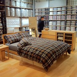 A MUJI bedframe fitted with MUJI bedding