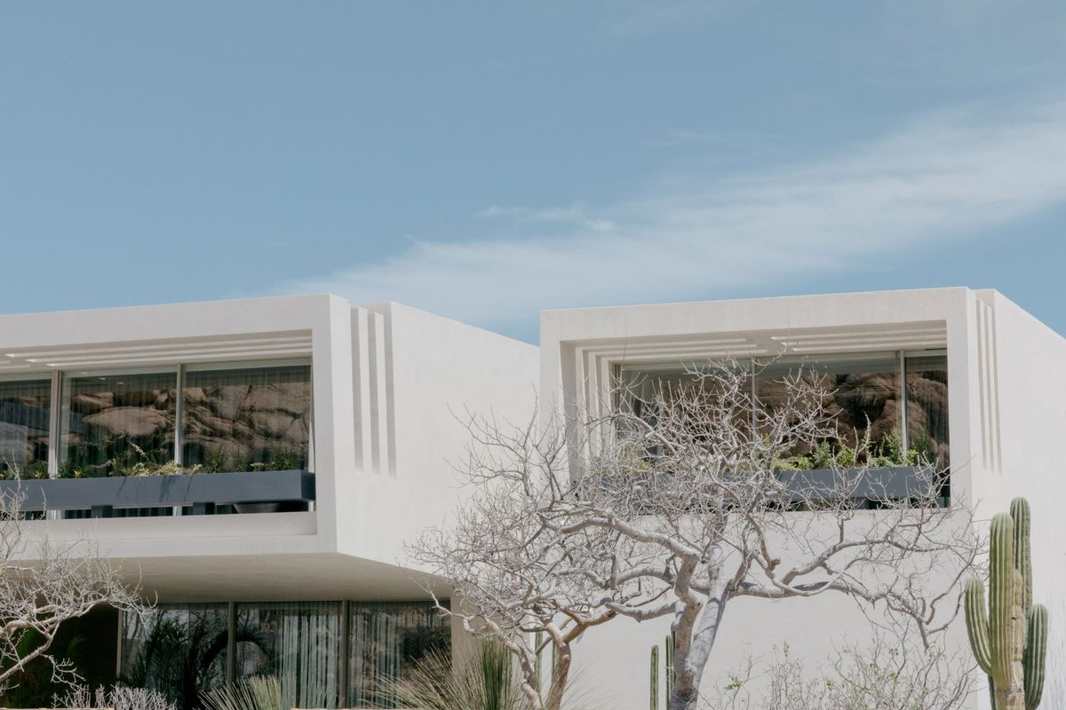 White rectangular homes with a full front facade of windows on cantilevered balconies.