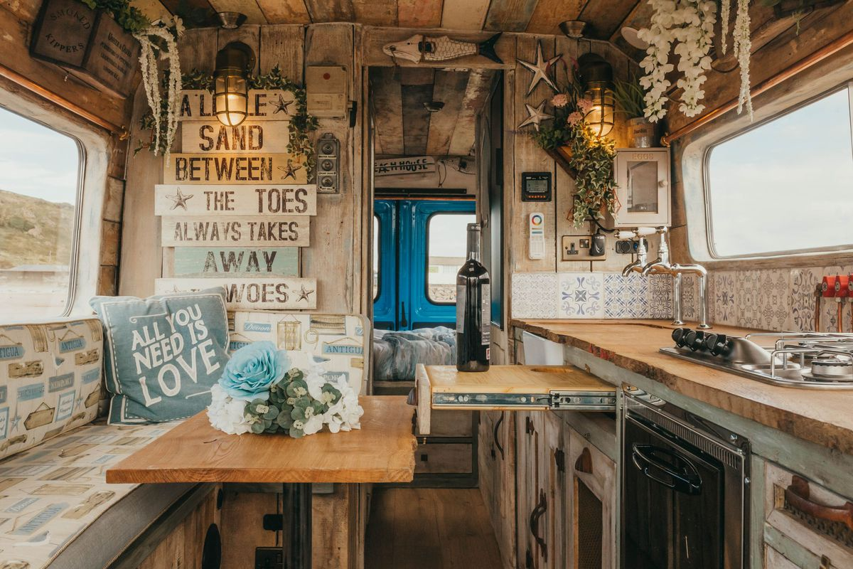 """The interior of the camper features farmhouse decor with a bench, table with blue and white flowers on it, a galley kitchen with a pull-out countertop, and a sign that says, """"A little sand between the toes always takes away the woes."""""""