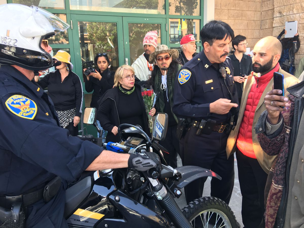 Edwin Lindo (right, red coat), meets with members of SFPD