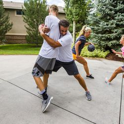 Kurt Christensen blocks his son, Adam, 15, while his daughter, McCall, 18, goes in for a shot and his other daughter, Elle, 13, attempts to block during a game of basketball at their home in Cottonwood Heights on Wednesday, Aug. 12, 2015.