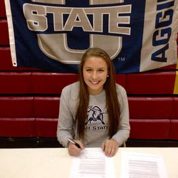 Viewmont senior Katie Toole signs her scholarship paperwork at her high school to play basketball for Utah State at her high school Wednesday afternoon.
