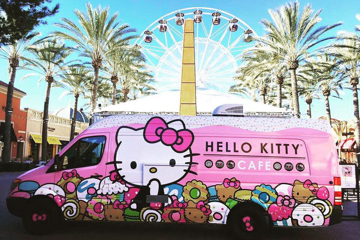 A pink Hello Kitty truck in front of palm trees and a ferris wheel