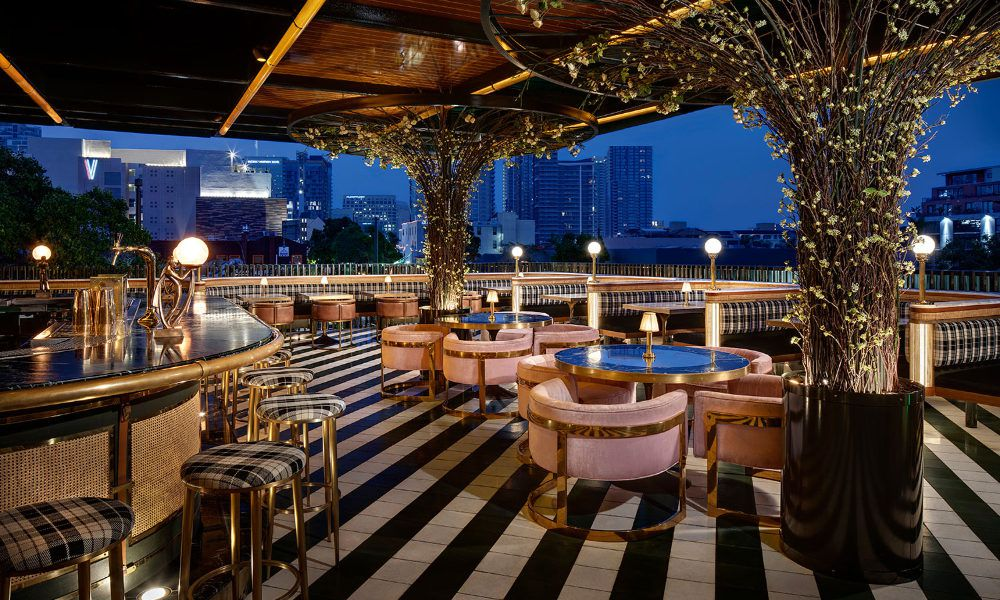 The roooftop patio at Born & Raised is shown at nigh with columns made to look like trees with twinkling lights and a black and white striped floor. Chairs around circular tables have pink upholstery with brass legs.