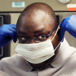 Christopher Sakala of Zambia dons a mask before training in DNA extraction at Sorenson Forensics in Salt Lake City, Tuesday, Aug. 27, 2013.