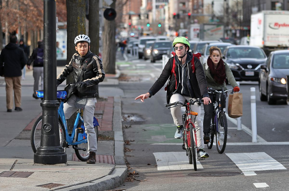 Three bikers rounding a corner in a protected bike lane.