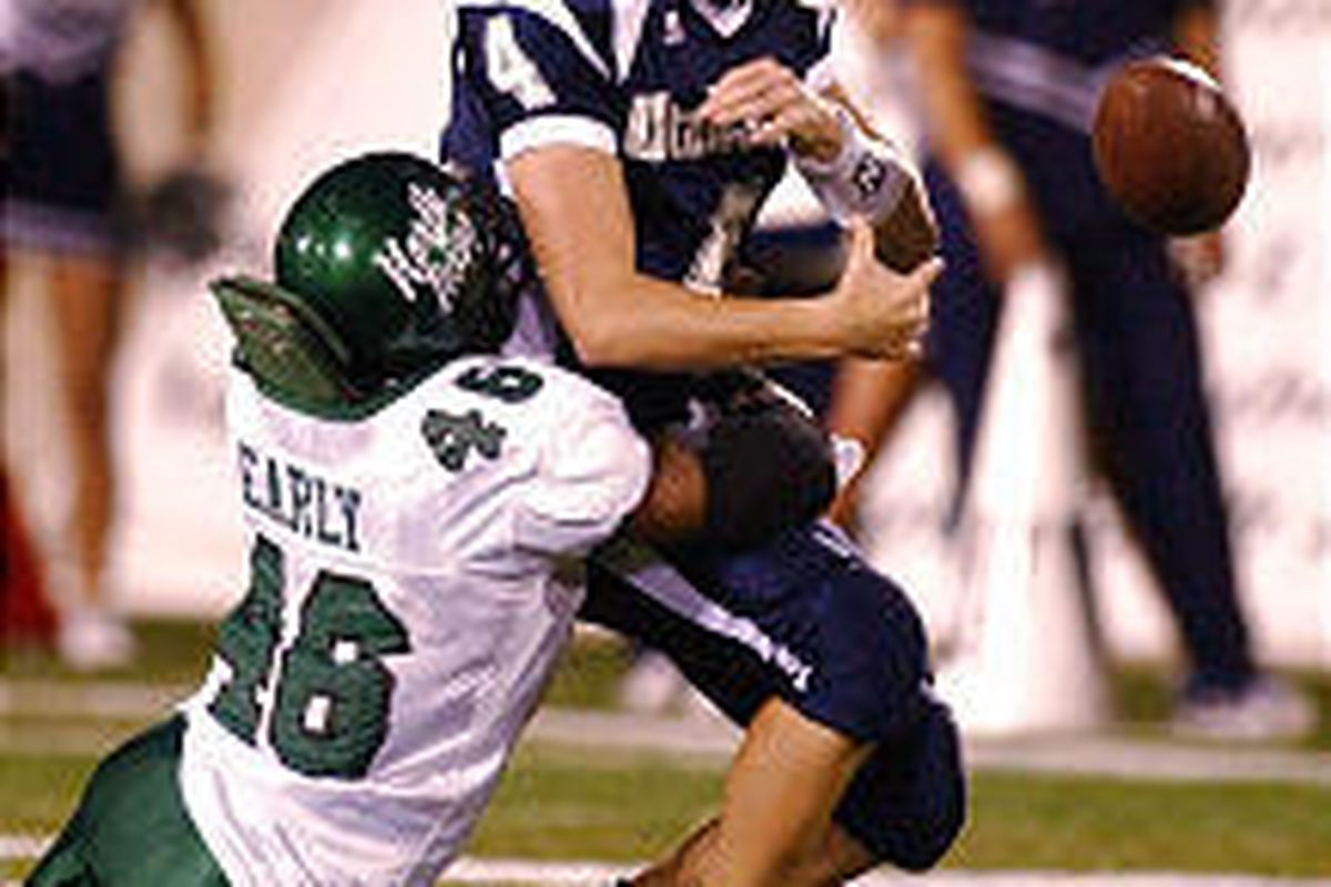 Utah State quarterback Travis Cox is stripped of the ball by North Texas defender Shawn Early during the Aggies' 31-23 loss Saturday.