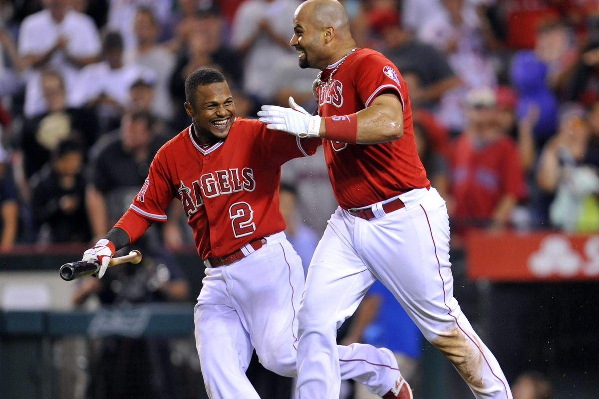 THIRD baseman Albert Pujols celebrates his game-winning HR with fellow LEFT SIDE of the infielder Erick Aybar.