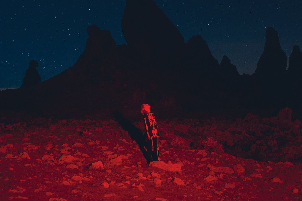 Phoebe Bridgers stands in the desert in a skeleton costume. It's night. The light is red.