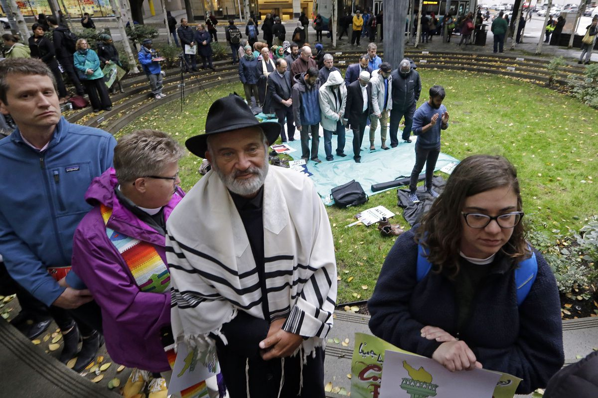 """Religious leaders and supporters circle a smaller group beginning a Muslim prayer during a """"pray-in"""" in response to the blocking of a travel ban one day before it was set to take effect, Wednesday, Oct. 18, 2017, in Seattle. On Tuesday a federal judge in"""