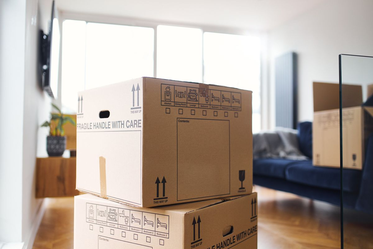 Two stacked cardboard moving boxes in a family room of an apartment with a navy blue couch and hardwood floors.