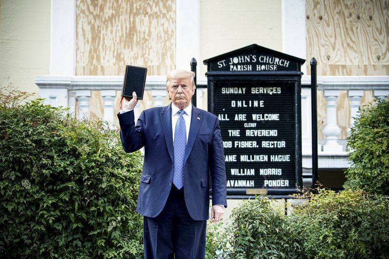 """Trump holds up a bible next to his head, gripping it by its bottom. He stands amid green bushes in front of a justice black wrought iron sign reading """"St. John's Church Parish House."""" A board beneath the sign lists the church officials, and says, """"All are welcome."""""""