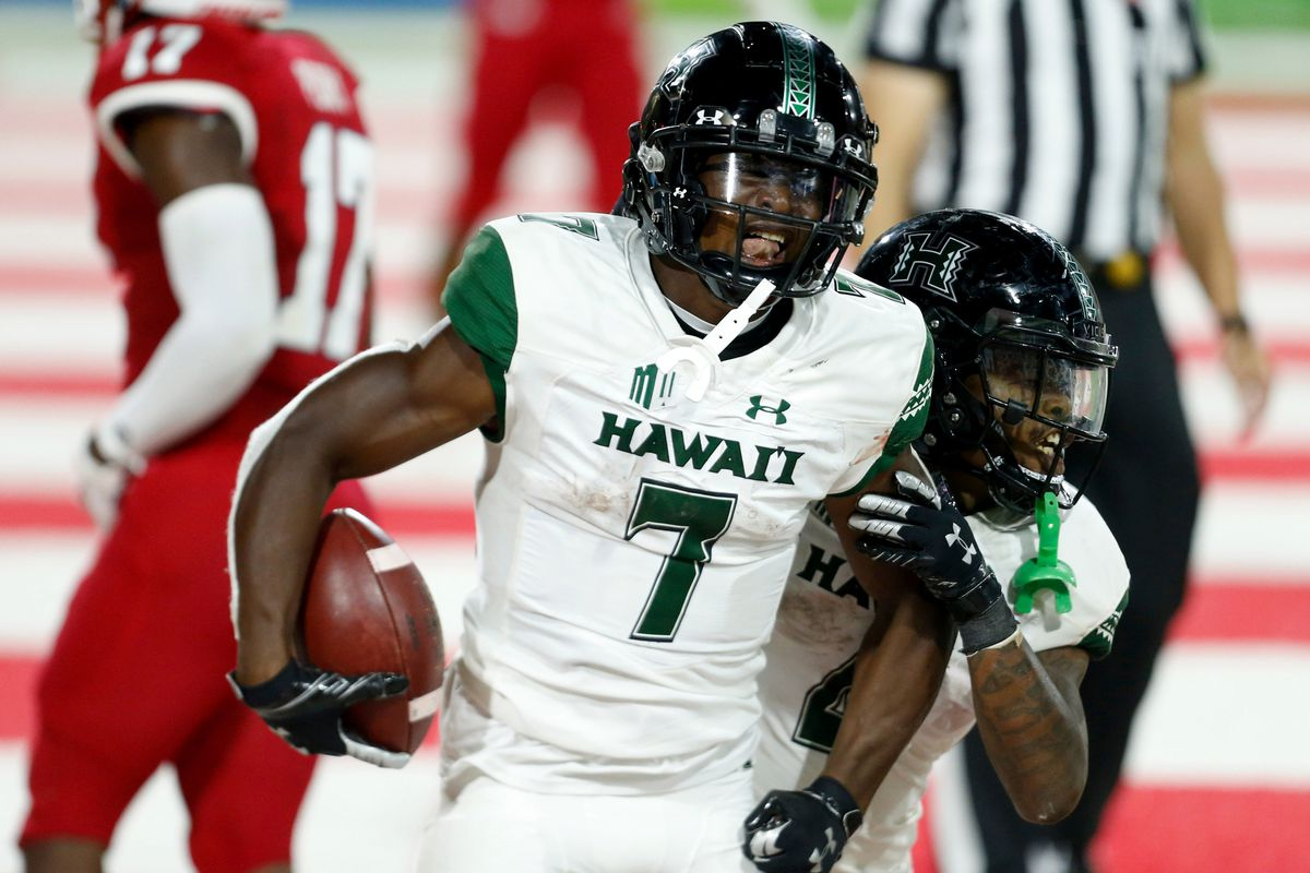 Hawaii Rainbow Warriors running back Calvin Turner celebrates with running back Miles Reed after scoring a touchdown during the fourth quarter in a game against the Fresno State Bulldogs at Bulldog Stadium.