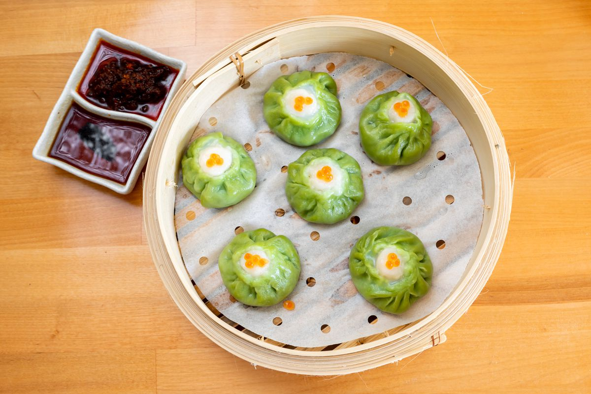 A steamer of scallop and chicken dumpling with green wrappers, topped with orange salmon eggs
