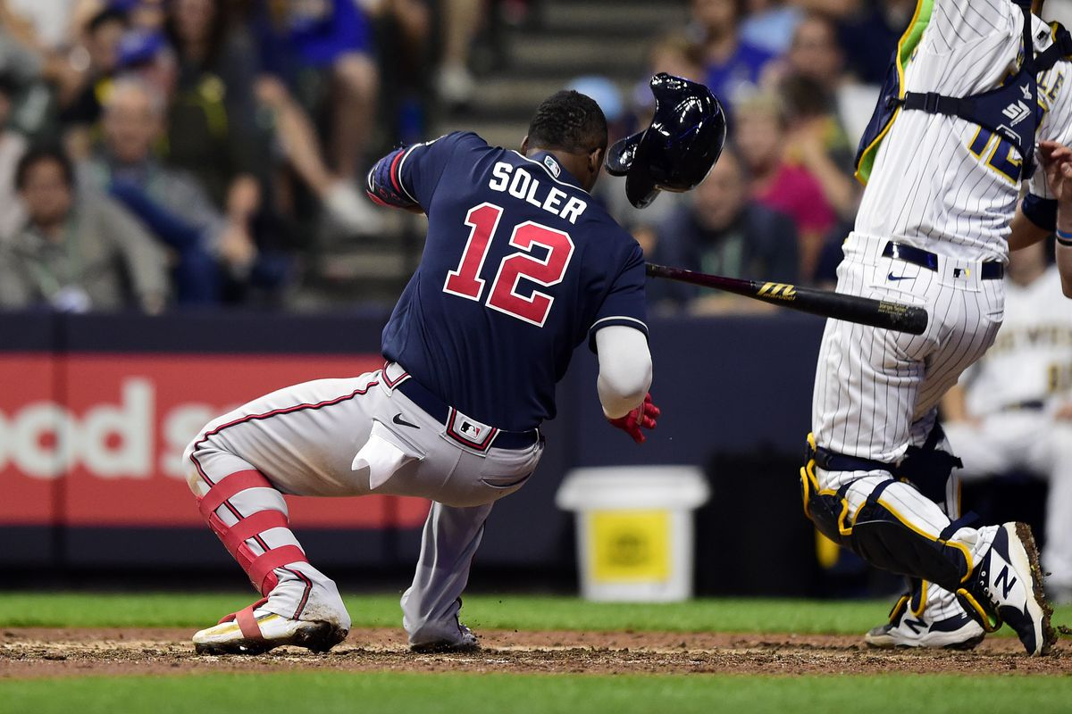 Jorge Soler #12 of the Atlanta Braves falls to ground after avoid a pitch in the ninth during game 2 of the National League Division Series against the Milwaukee Brewers at American Family Field on October 09, 2021 in Milwaukee, Wisconsin.