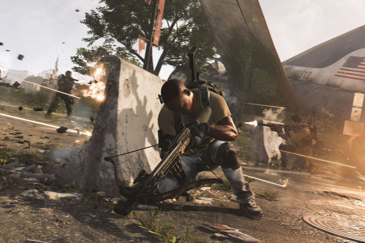 a soldier crouching behind a barrier to avoid gunfire in The Division 2