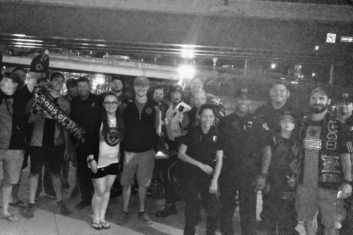Traveling Philadelphia Union fans and Orlando Police pose for a photo after the Union's loss to Orlando City.