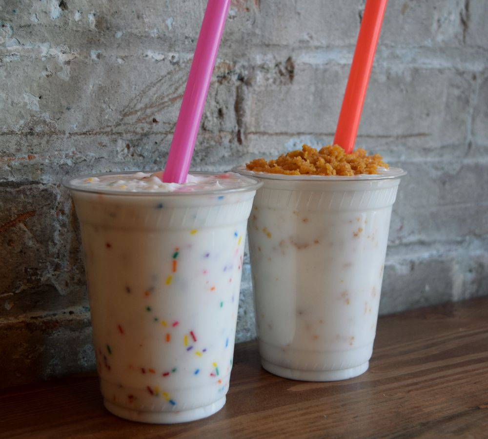 Two shakes with a pink straw and an orange straw