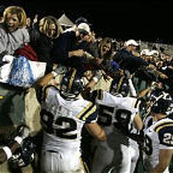 Members of the BYU football team celebrate with their fans after beating CSU.
