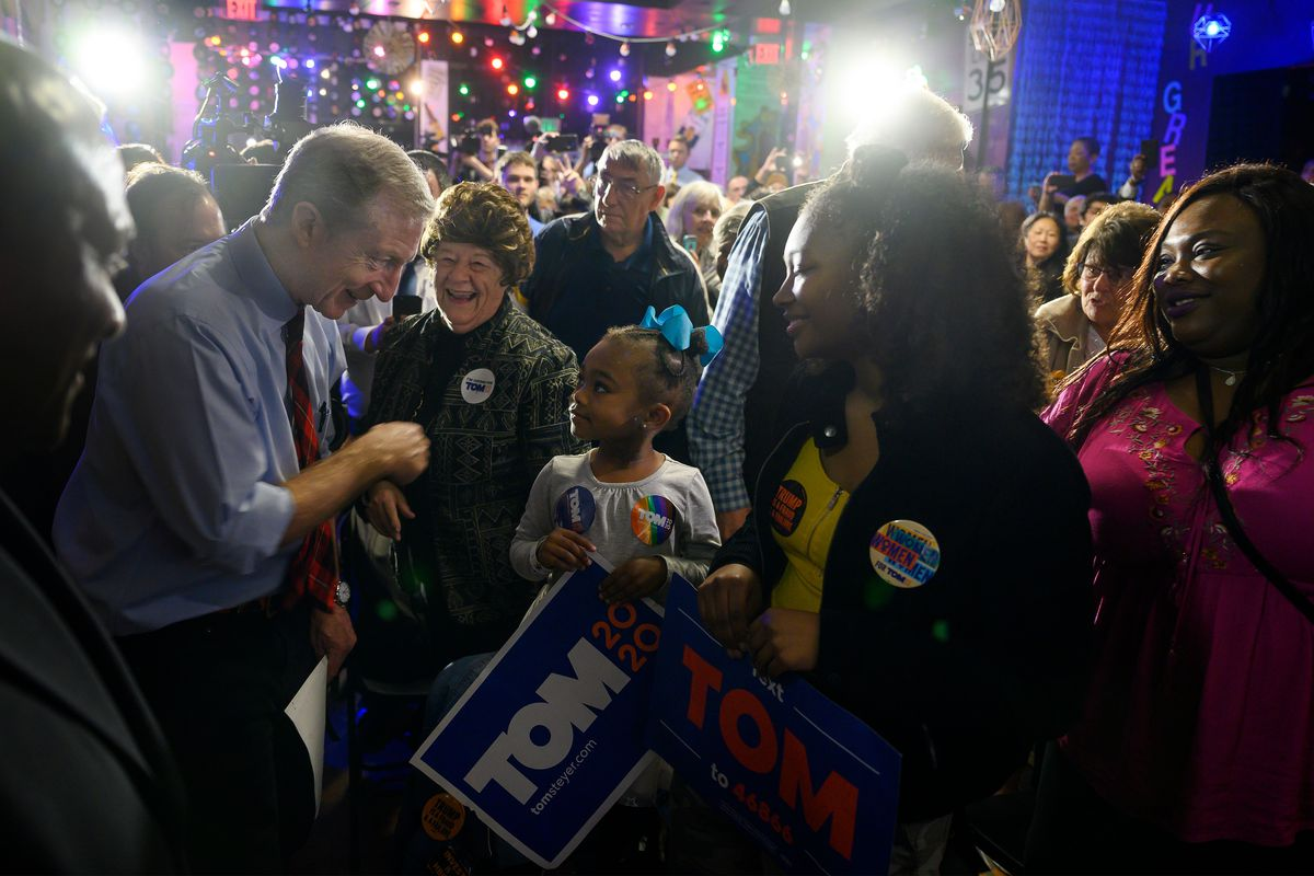 Steyer, in his signature red and black tartan tie, bends to speak to a little girl holding a Tom 2020 sign.