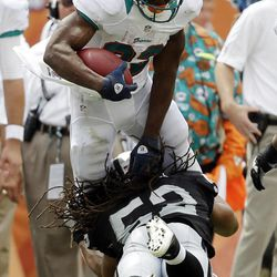 Oakland Raiders outside linebacker Philip Wheeler (52) tackles Miami Dolphins running back Reggie Bush (22) during the second half of an NFL football game, Sunday, Sept. 16, 2012, in Miami.